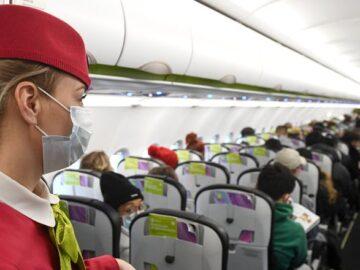 Бортпроводница в маске в салоне самолета